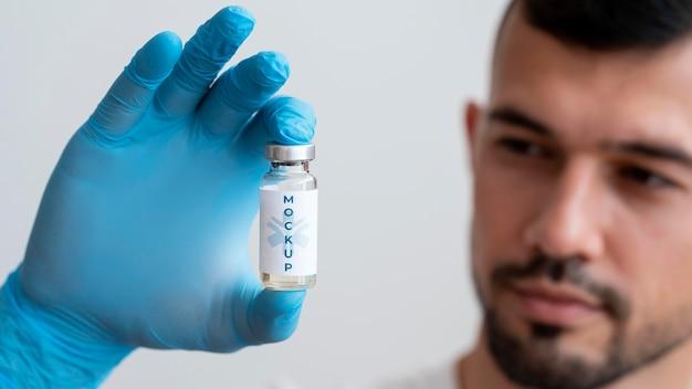 Mens die een vaccinfles bekijkt