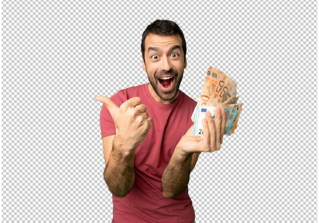 Mens die heel wat geld neemt dat duimen op gebaar met beide handen en het glimlachen geeft
