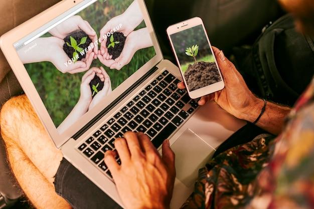 Mens die laptop en smartphonemodel met aardconcept met behulp van