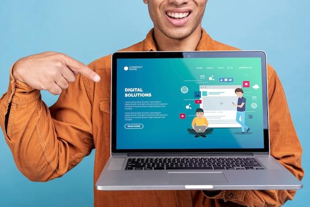 Mens die laptop met een digitale oplossingslandingspagina houdt