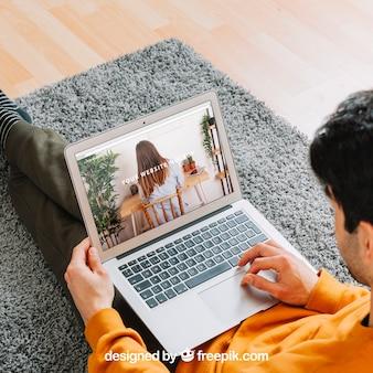 Mens die laptop op vloer met behulp van