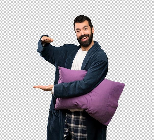 Mens die met baard in pyjama's copyspace houden om een advertentie op te nemen