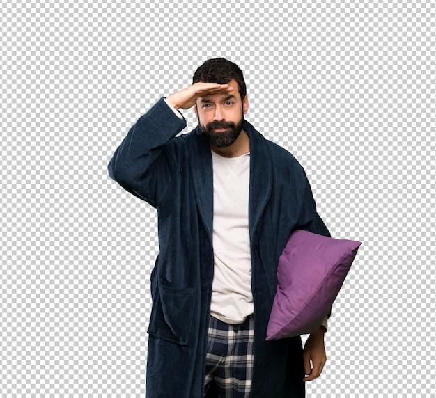 Mens die met baard in pyjama's ver weg met hand kijken om iets te kijken
