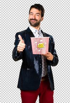 Mens die met jasje popcorns eet