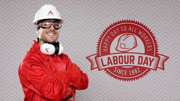 Mens in rood die de arbeidsdag van de bouwhoed dragen