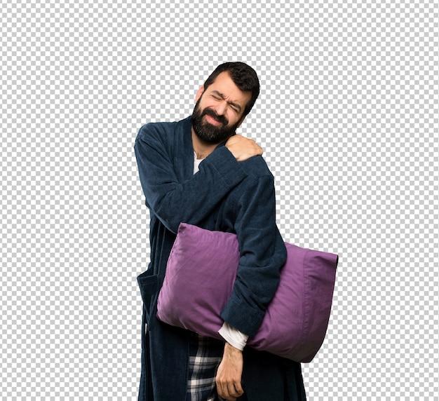 Mens met baard in pyjama die aan pijn in schouder lijden voor het hebben van een inspanning