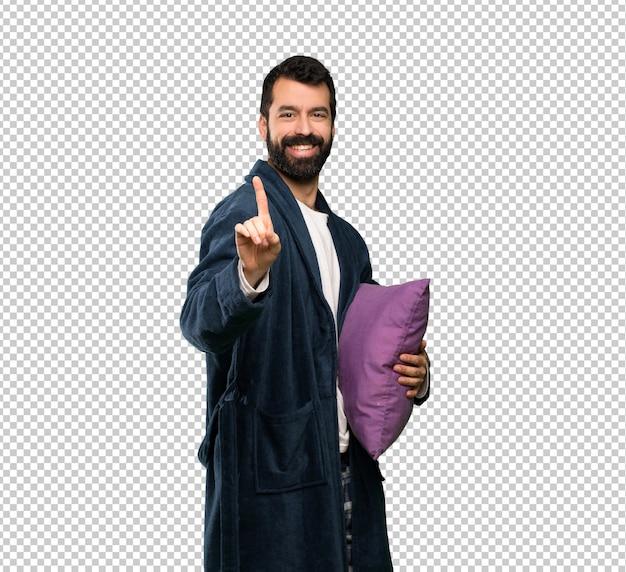 Mens met baard in pyjama die en een vinger toont opheft