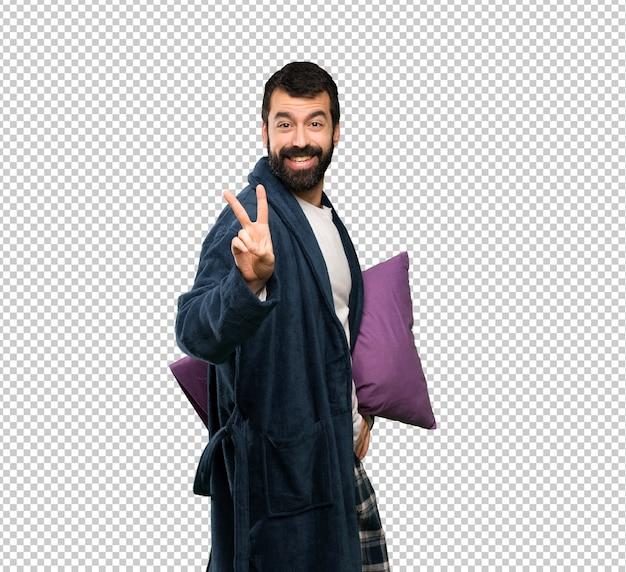 Mens met baard in pyjama die en overwinningsteken glimlacht toont