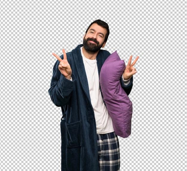 Mens met baard in pyjama die overwinningsteken met beide handen tonen