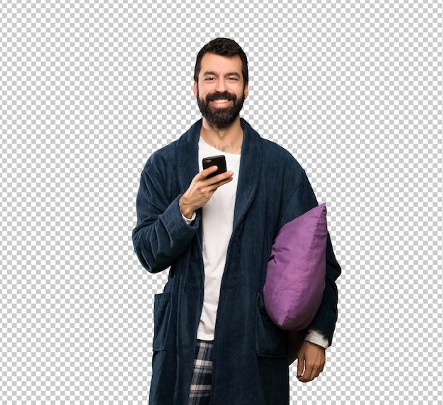 Mens met baard in pyjama's die een bericht met mobiel verzenden