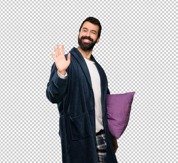 Mens met baard in pyjama's die met hand met gelukkige uitdrukking groeten