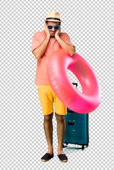 Mens met hoed en zonnebril op zijn de zomervakantie die beide oren behandelen met handen. gefrustreerde uitdrukking