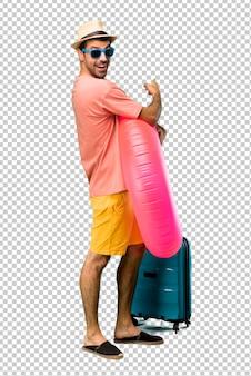 Mens met hoed en zonnebril op zijn de zomervakantie die terug met de wijsvinger richten die een product van erachter voorstellen