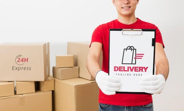 Mensajero con portapapeles delante de maquetas de paquetes
