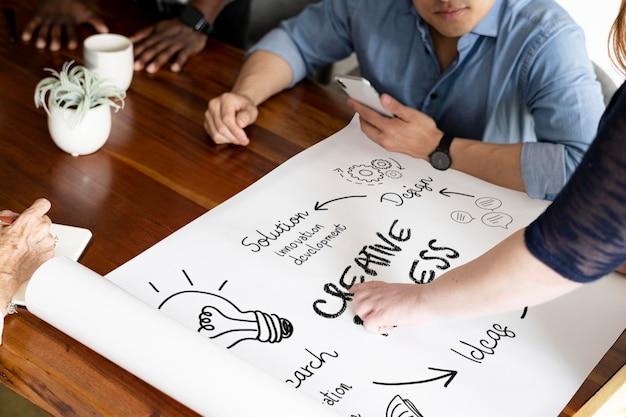Mensen uit het bedrijfsleven doen creatieve zaken op een papieren mockup