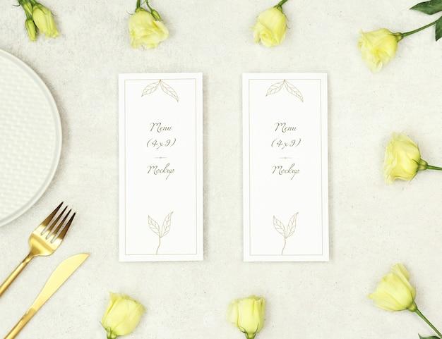 Menú de boda de maqueta con flores y cubiertos de oro.