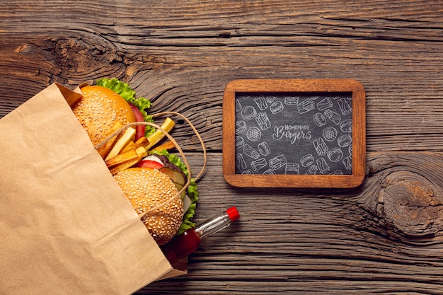 Menú de hamburguesas en bolsa de papel sobre fondo de madera y marco de fondo de madera