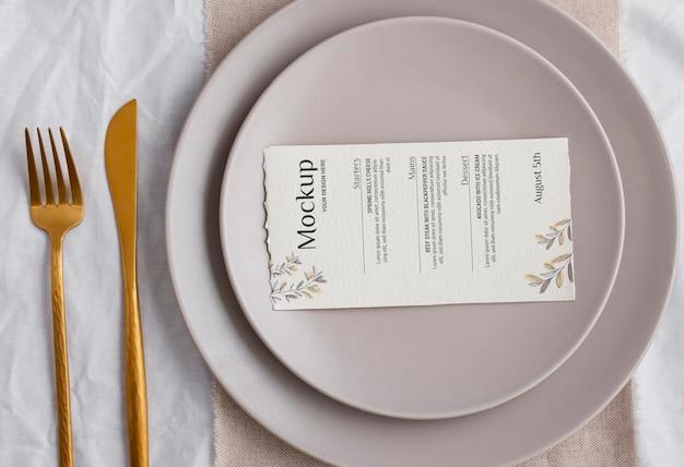 Menú de primavera con platos y cubiertos dorados.