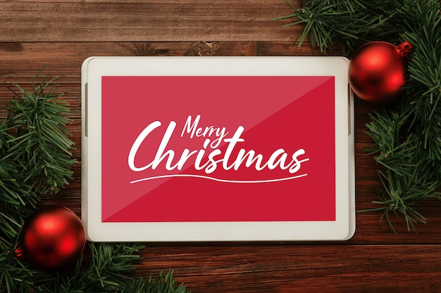 Merry christmas tabletcomputer mockup sjabloon met decoraties van dennenbladeren.
