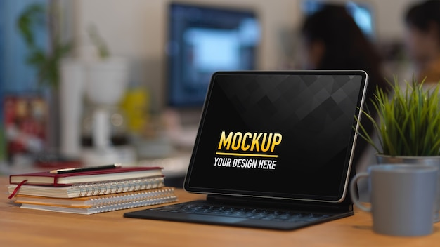Mesa de trabajo con maqueta de tableta digital, cuadernos y maceta en la habitación de la oficina