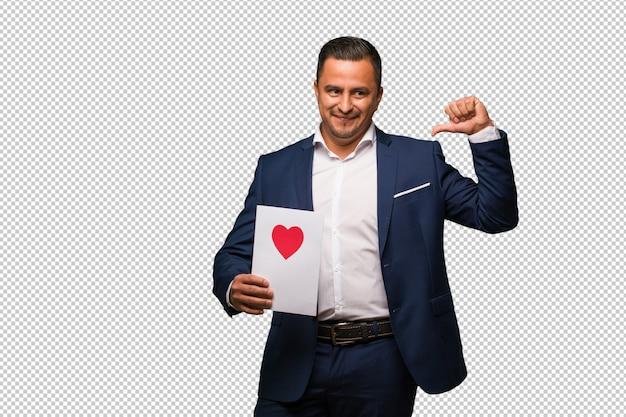 Middelbare leeftijd latijns-man vieren valentijnsdag wijzende vingers, voorbeeld te volgen
