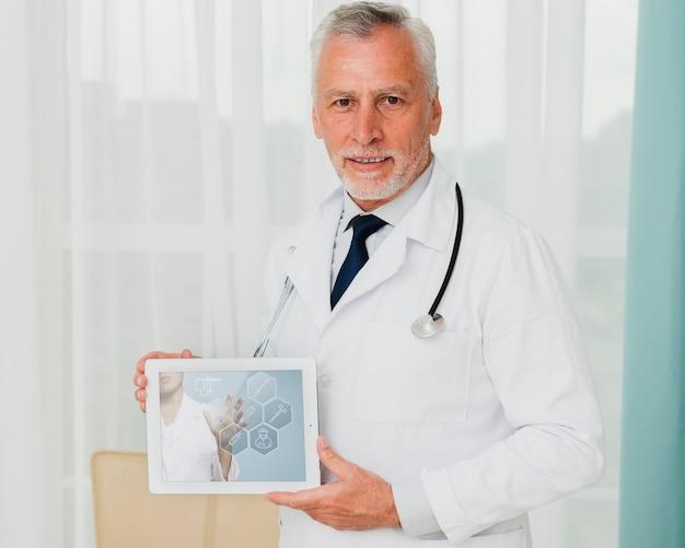 Middelgroot schot van mannelijke arts die een tablet houdt