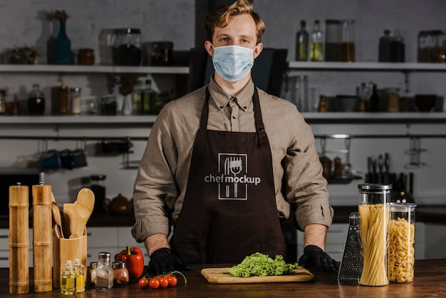 Middelgrote chef-kok die gezichtsmasker draagt