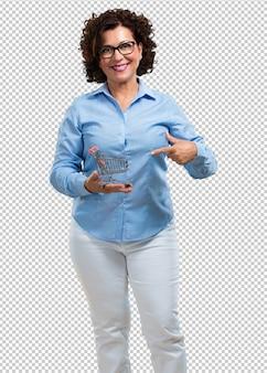Midden oude en glimlachende vrouw die, een miniatuurboodschappenwagentje, concept het winkelen, consumentisme houden glimlachen