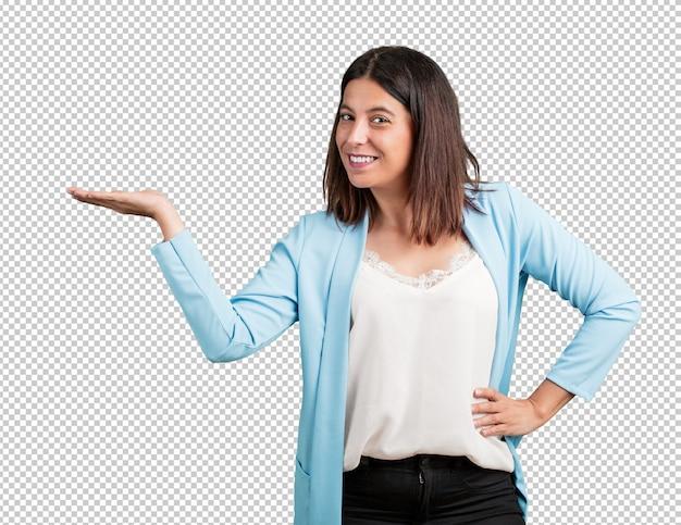 Midden oude vrouwenholding iets met handen, die een product toont, glimlachend en vrolijk