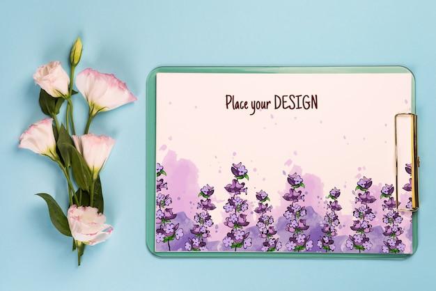 Minimale compositie met een eustoma-bloemen in een envelop met klembord op blauw papier