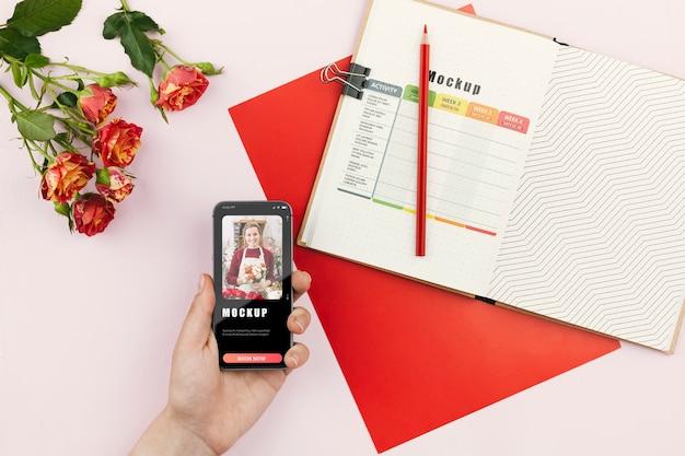 Mobiel naast agenda en bloemen op bureau