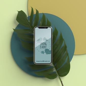 Mobiel op 3d blad op tafel