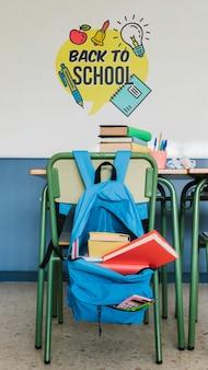 Mochila de regreso a la escuela con útiles y maqueta de pared