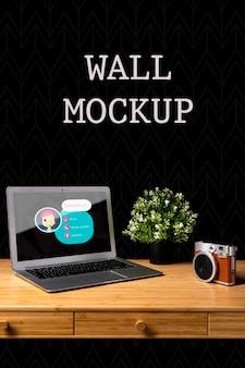 Mock-up a parete con fotocamera e laptop