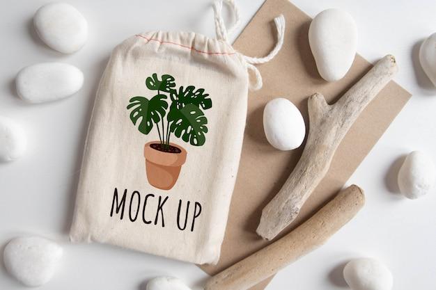 Mock up de bolsa de algodón cubierta de tarot con sobre de papel artesanal de textura marrón y palo rústico en mesa blanca