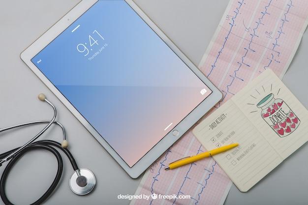 Mock up con tavoletta, stetoscopio, cardiogramma e notebook