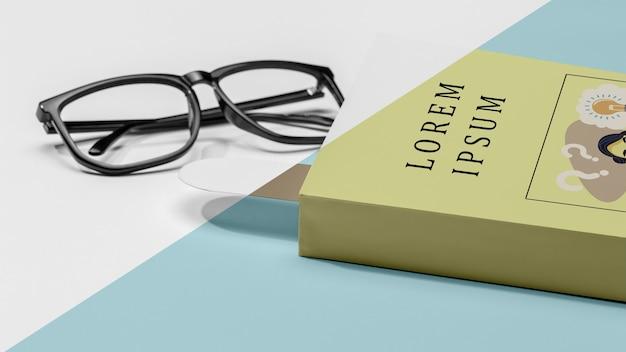 Mock-up del libro del primo piano con gli occhiali