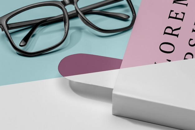 Mock-up del libro del primo piano con occhiali e segnalibro