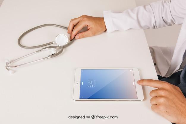 Mock up design con medico che lavora con il tablet