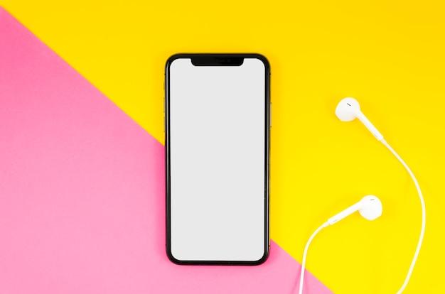 Mock-up di smartphone con vista dall'alto con auricolari