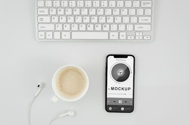 Mock-up di smartphone piatto laici con tazza e auricolari sulla scrivania