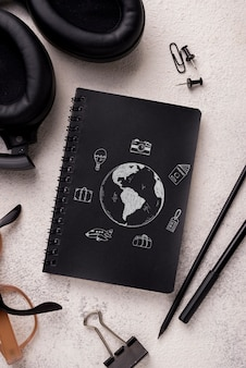 Mock-up e penna per notebook flat lay vicino con occhiali e cuffie