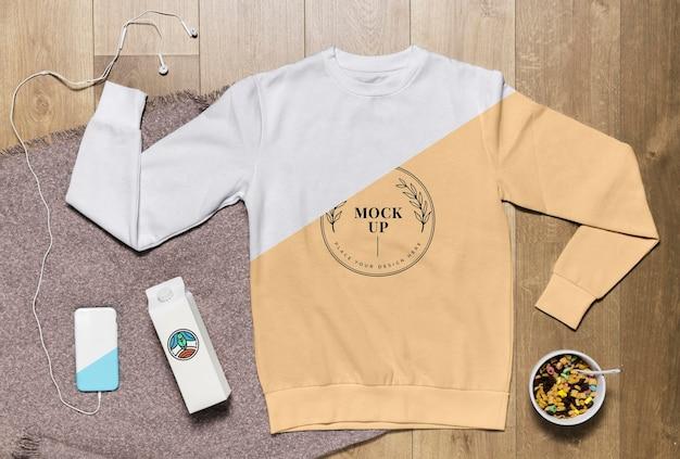 Mock-up felpa con cappuccio vista dall'alto con snack e custodia per telefono