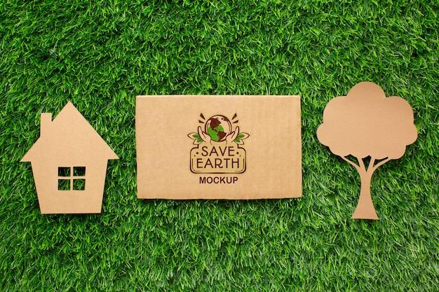 Mock-up in cartone ecologico vista dall'alto con casa di carta e albero