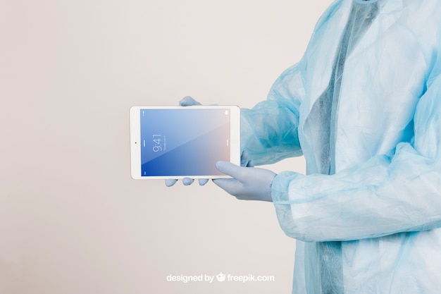 Mock up met de handen van de chirurg met een tablet