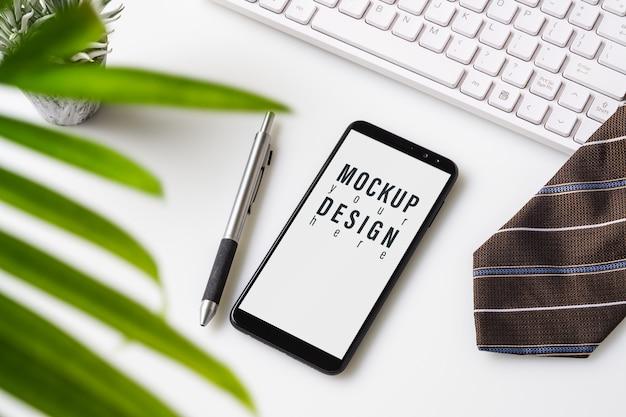 Mock-up smartphone. bovenaanzicht van bureau tafel met grafiek grafiek.