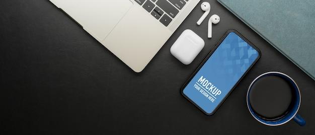 Mock-up smartphone op zwarte tafel met laptop, oortelefoon en kopie ruimte in kantoorruimte