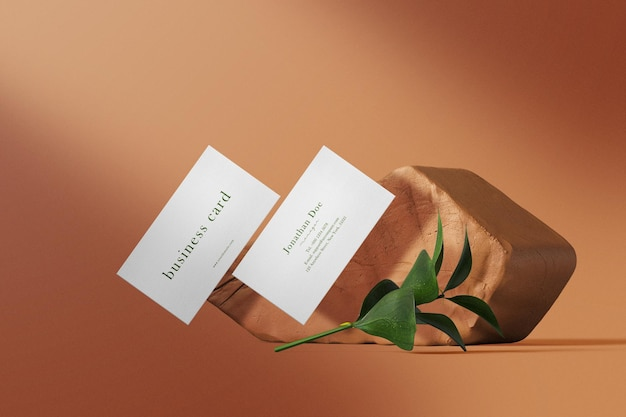 Mock up de tarjeta de visita mínima limpia flotando en terracota con hojas