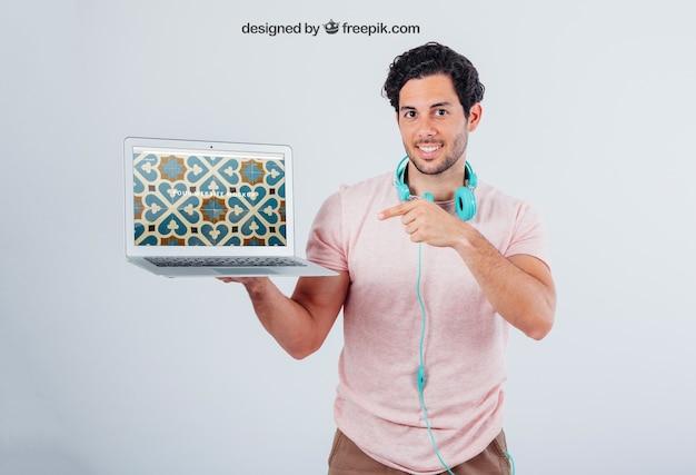 Mock up van het scherm van de laptop en de jonge man wijst