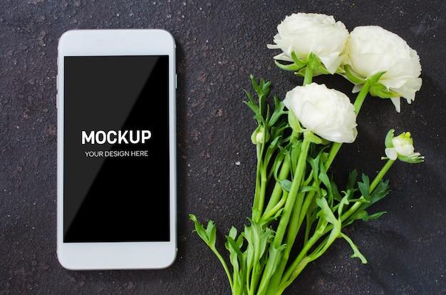 Mock up van smartphone scherm en witte bloemen op donkere betonnen muur.